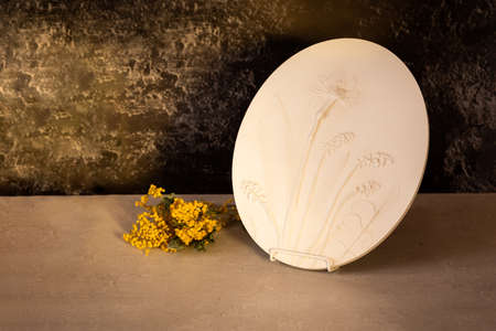 Stylish living room interior with botanical bas-relief spring flowers daffodils for wall art and flowers mimosa. 3D Flower plaster decor. Modern and luxury interior of room.
