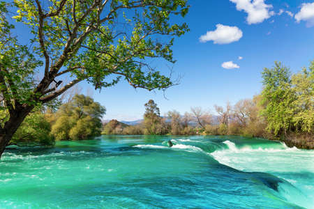 Beautiful natural landscape of Manavgat waterfall in national park on sunny spring day. Unique azure water color with splashes, Side, Antalya,Turkey