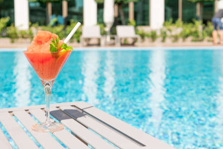 Fresh red cocktail with ice in glass on swimming pool. Tropical juice on luxury vacations. Concept summer holiday and travel.