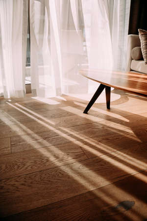 Modern room interior with an open window in minimal style. Transparent tulle with morning sun rays on shadow background. Vertical photo 版權商用圖片