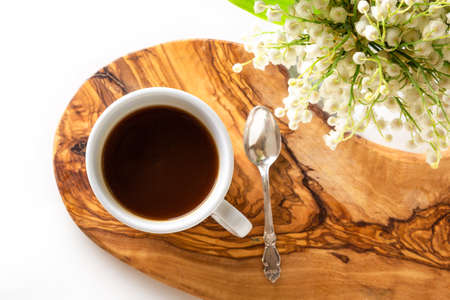 Cup of coffee and fresh bouquet of blooming lily of valley flowers on wooden stand on white background. Top view, flat lay, copy space