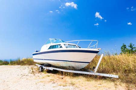 Old boat on sandy beach on coastline of Adriatic Sea, Montenegro.