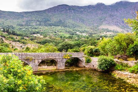 Old stone bridge over small transparent river at foot of mountains, near Risana, Boca-kotor bay, Montenegro 版權商用圖片