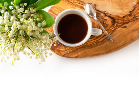 Cup of coffee and fresh bouquet of blooming lily of valley flowers on wooden stand on white background. Top view, flat lay, copy space.