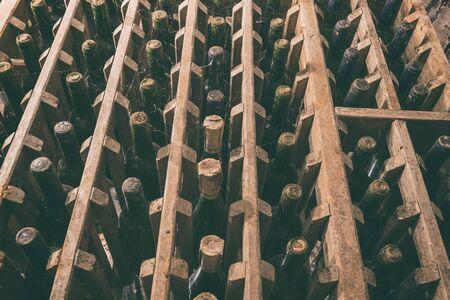 Old wine bottles in the wine cellar, blurred defocused background