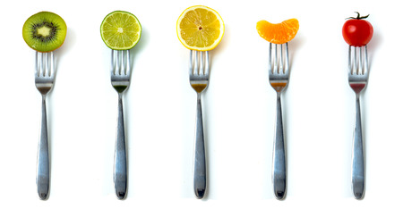 Mix of fruits and vegetables on forks in white background  photo