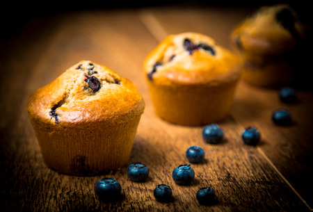 Blueberry muffins isolated on wood table  photo