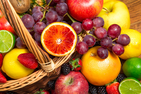 Mix of fresh fruits on wicker basket photo