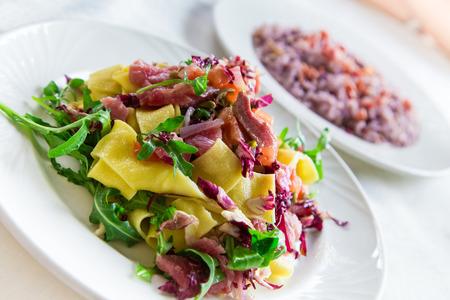 Homemade tagliatelle with fresh tuna served with cherry tomatoes, radicchio and arugula Stock Photo
