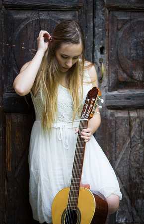 Pretty blonde girl in white dress playing guitar on rural outdoor Stock Photo