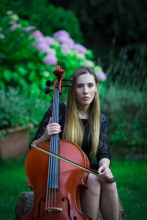 Pretty blonde girl in black dress playing a cello in a rural outdoor