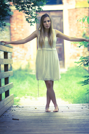 Beautiful young blonde girl with white dress walking in the garden on sunset scenario