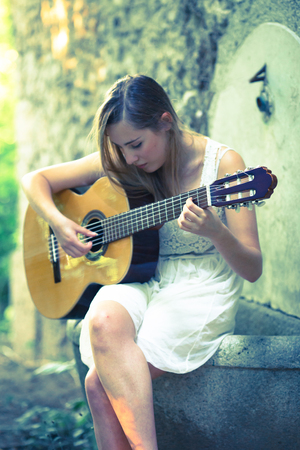 Beautiful young blonde girl with white dress playing a guitar in a sunset scenario Stock Photo