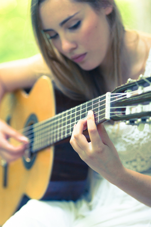 Beautiful young blonde girl with white dress playing a guitar in a sunset scenario Archivio Fotografico