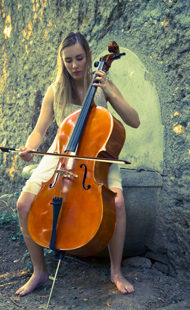 Beautiful young blonde girl with white dress playing a cello in a sunset scenario
