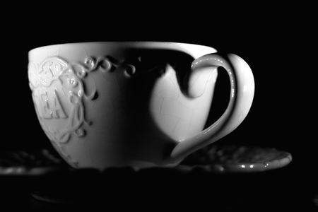 blackness: porcelain cup of tea with an inscription by candlelight