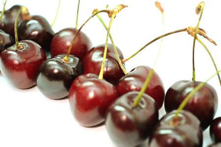 白い背景に分離された熟した赤い桜の果実