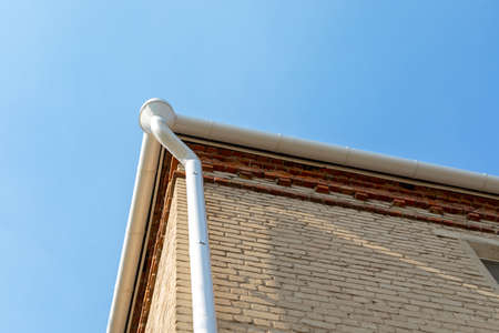 White metal pipe from the drain on the wall of a brick building. Holder gutter drainage system on the roof. Drain on the roof of the house. Roof drainage. Water drainage from the roof. 版權商用圖片