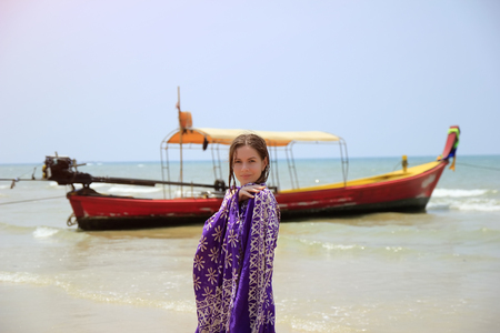 Portrait of woman on tropical beach, near traditional Thai boat. Thailand Stock Photo