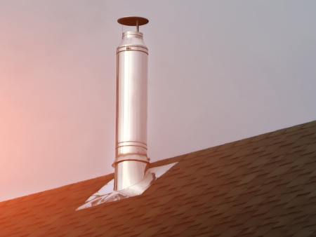 stove pipe: Chimney on tile roof. Red sky sunset