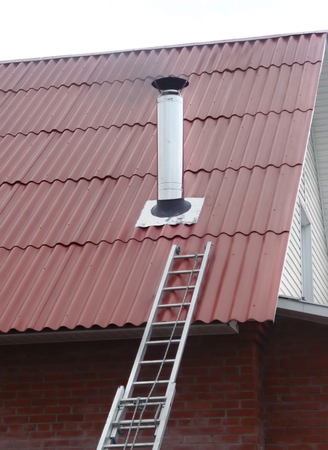 attic: Red metal roof with steel chimney pipe