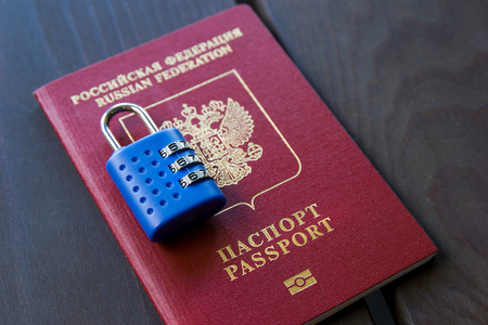 Russian passport locked to padlock. Symbol of anti-Russian sanctions.