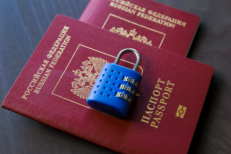 Two Red Passports with a blue lock on a wood background. Stock Photo