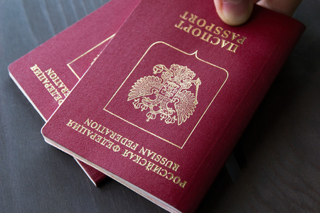 Male hand on top of red passports on a grey wood background.