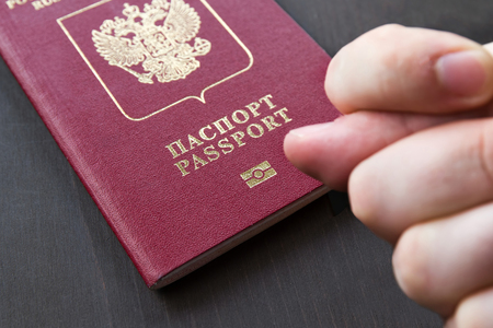 Hand showing the fig sign, on red russain passport background.