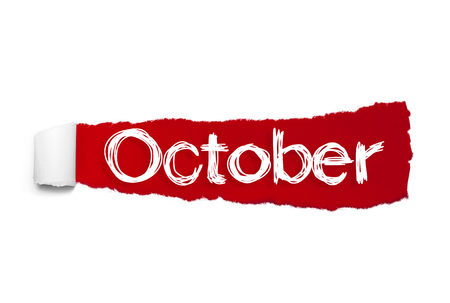 The word October appearing behind red torn paper.