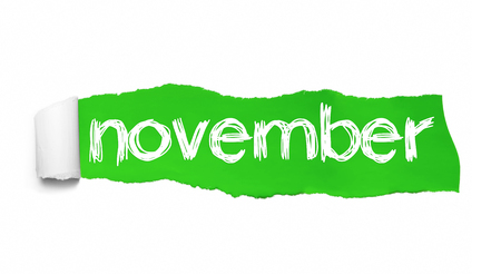 NOVEMBER word written under the curled piece of Green torn paper. Stock Photo