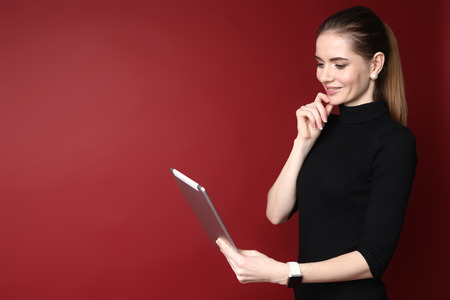 Portrait of a beautiful smiling caucasian woman working on tablet isolated on a red background Stock Photo