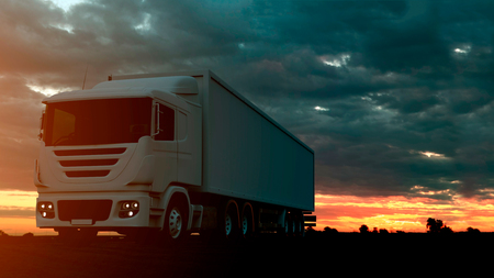 Large freight truck driving on a highway at sunset backlit by a bright orange sunburst under an ominous cloudy sky. 3d Rendering Imagens - 124874148