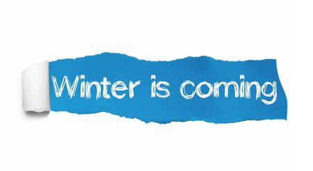 The text Winter is coming written under the curled piece of Blue torn paper. Stockfoto