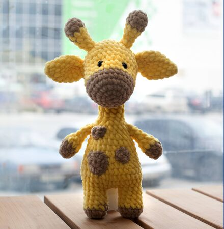 Crocheted amigurumi yellow giraffe. Knitted handmade toy.