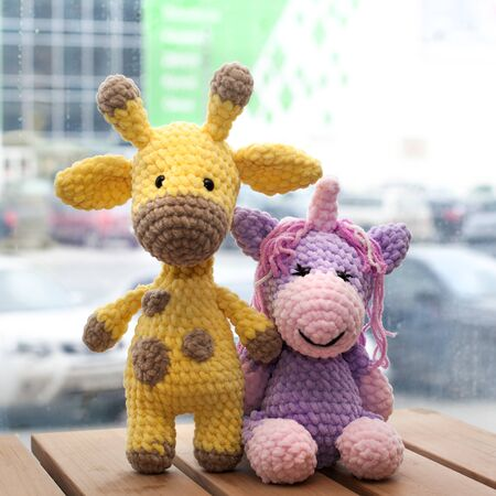 Crocheted amigurumi yellow giraffe and unicorn. Knitted handmade toy. Stockfoto
