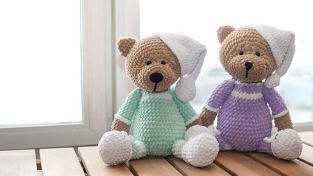 Two Brown stuffed animals teddy bear on wood table. Knitted handmade toys.