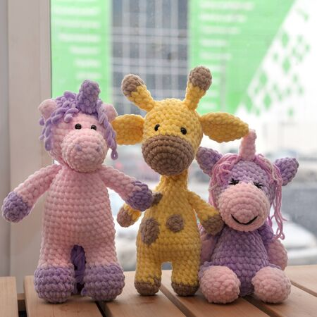 Handmade knitted toys. Yellow giraffe and two unicorns.