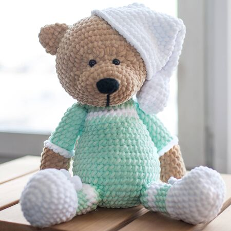 Handmade amigurumi teddy bear on wooden table.