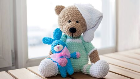 Handmade amigurumi teddy bear and rabbit on wooden table.