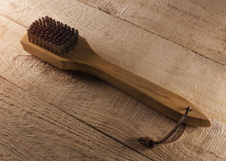 Barbecue grill cleaning brush on rustic wood background.