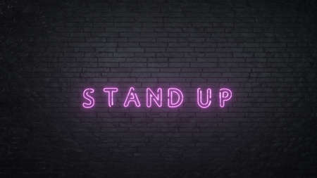 Stand Up neon sign on black brick wall background. 3d rendering.
