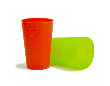 large group of items: Glasses of colored plastic. Glasses plastic two colors. Photo on a white background. Stock Photo