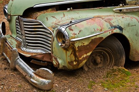 A green car grounded into the dirt with a twisted hood, grill and bumper.  Фото со стока