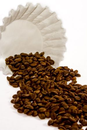 A bunch of coffee beans spilling out of a white filter on a white hi-key background