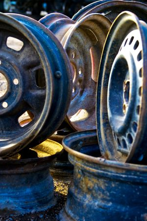 A grouping of rusting chrome wheels in high contrast with great lighting