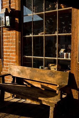 A wooden walk with a bench, gift store window, and lantern in Old Town, San Diego, California Фото со стока