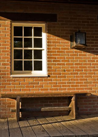 A wooden bench, white paned window, and a brick wall in front of an old building in Old Town, San Diego, California