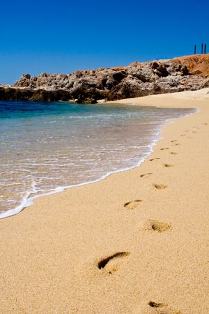 Footprints in the sand as the waves flow in