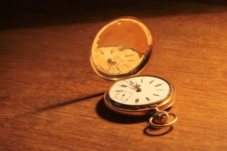 escapement: Antique vintage gold pocket watch closeup on a background of old wood